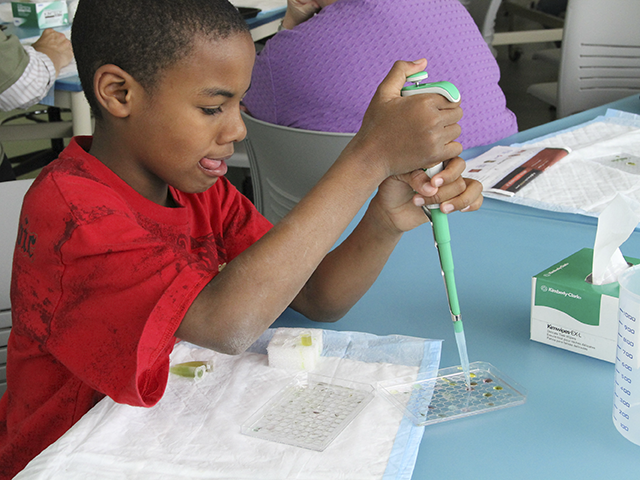 Boy learning to use a pipette in the Micro World Investigate Lab