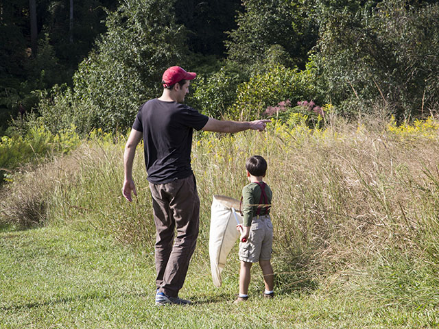 A father points out to his son a good spot to swing the bug net at Take a Child Outside at Prairie Ridge 2014.
