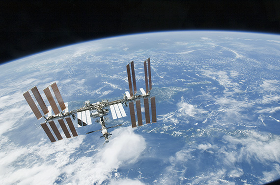The International Space Station, backdropped by Earth's horizon and the blackness of space.