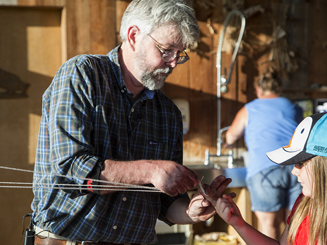 Museum educator Bob Alderink makes rope during a survival skills class