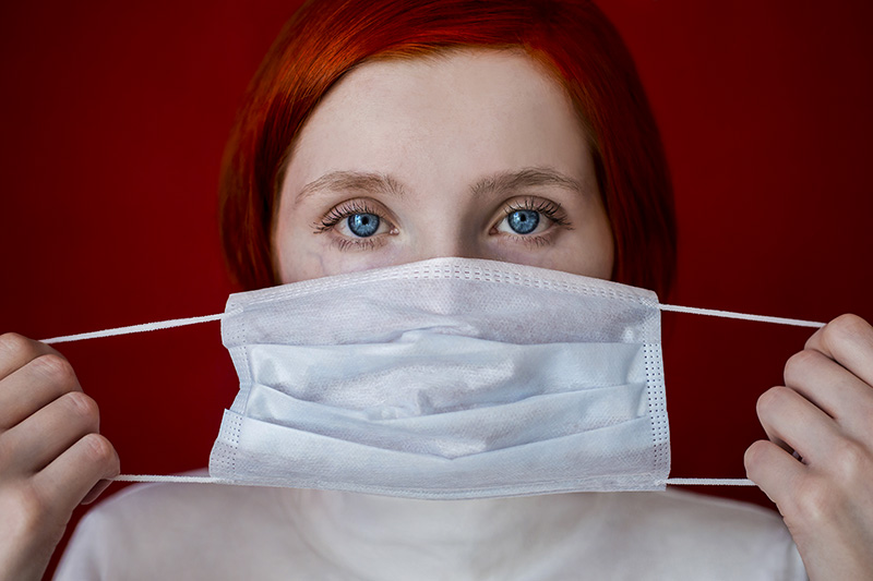 Red-haired girl holding a medical mask.