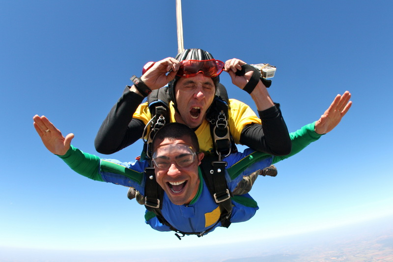 A parachutist makes a face and the other shouts in happiness.
