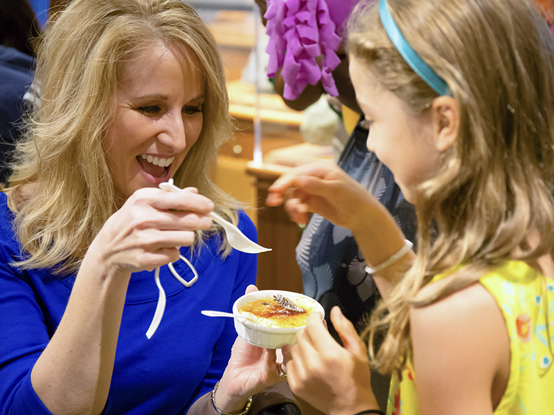 WRAL's Debra Morgan offering a bite of bug-festooned crème brûlée to a young girl. Photo: Matt Zeher.