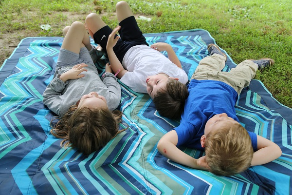 Children lounge on a blanket under a summer sky.