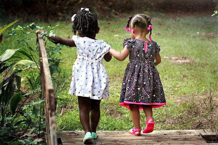 Two little girls in braids hold hands and go for a lovely walk outdoors.