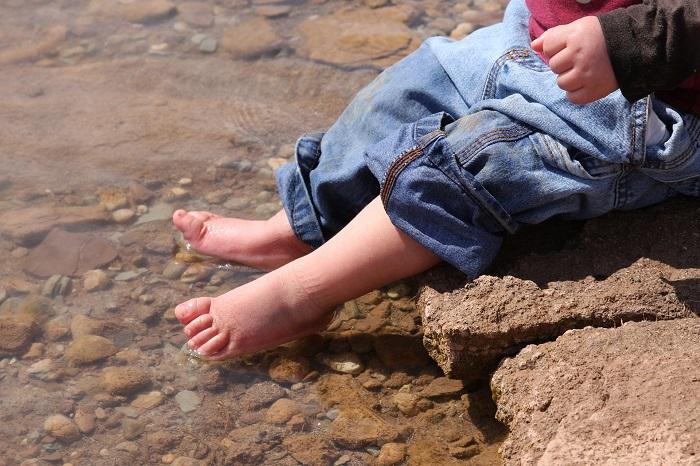 A baby's feet splash in a clear stream.