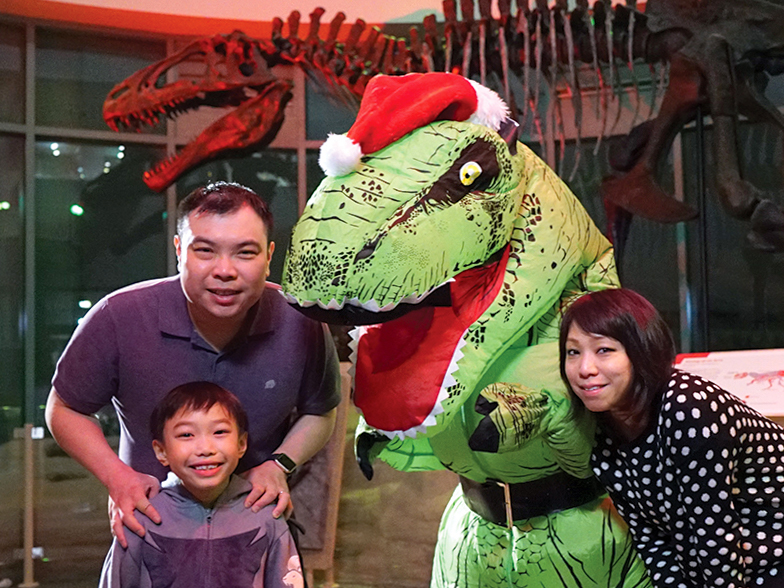 A family of 3 stands smiling around a dinosaur dressed in a red Santa Claus hat.