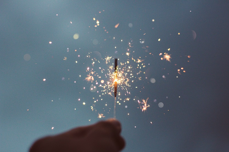 Sparklers glimmer different soft pastel colors from a sparkler. Pink, yellow, white and blue sparks shoot from the sparkler, held between the close-up fingers of a silhouette person.