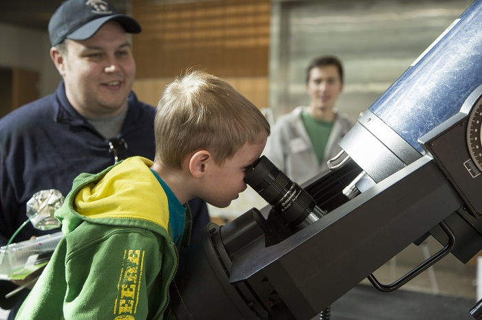 Young kid gazes into a microscope as his father smiles behind him.