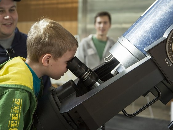 Child curiously peers into a large telescope.