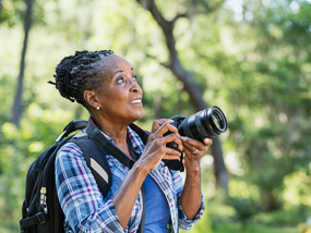 A senior African-American woman taking photos in a park.