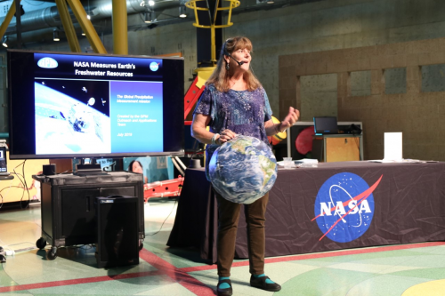 A woman from NASA giving a presentation with an Earth beach ball