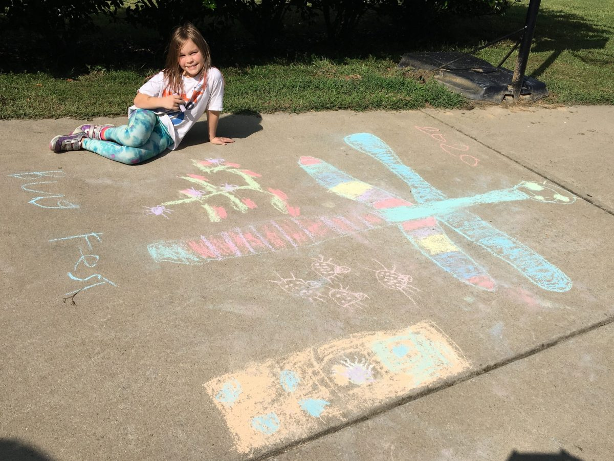 a little girl with a big chalk dragonfly