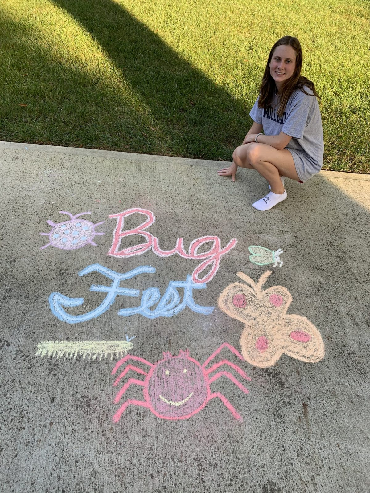 a young woman by a cursive bugfest and an assortment of chalk bugs