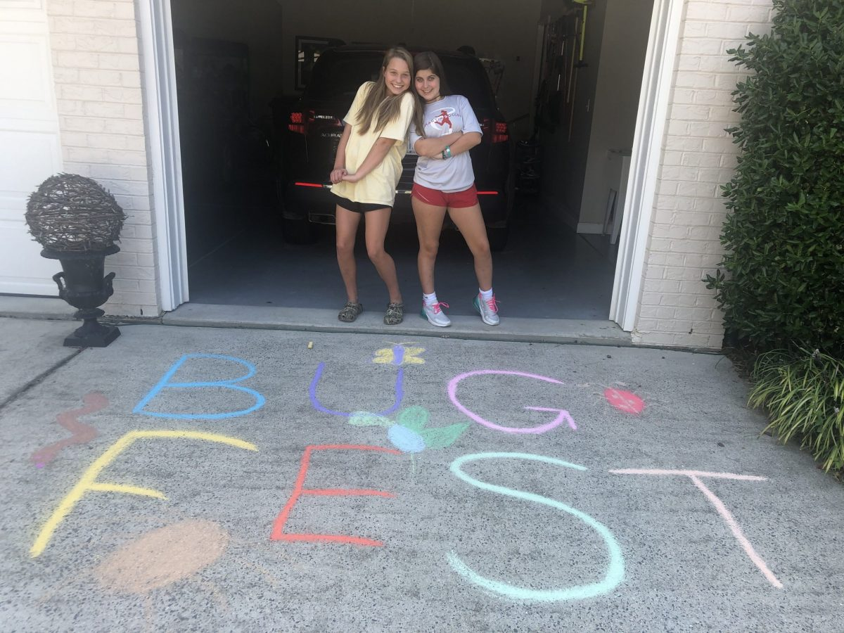 Two girls with BugFest in chalk on the driveway