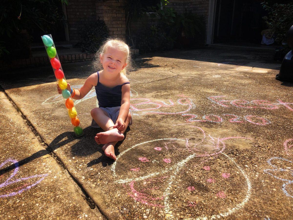 A little girl with sidewalk chalk