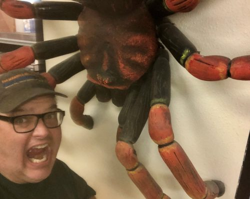 a man screaming at a giant fake spider