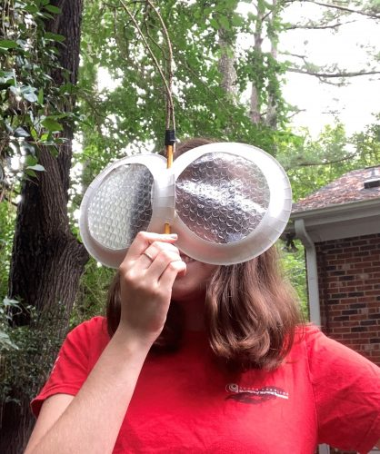 A woman holding homemade fly eyes up to her face