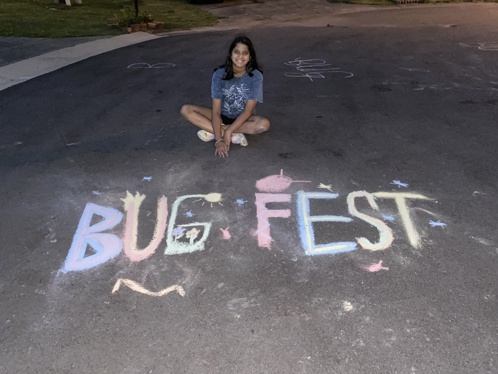 A girl sitting cross-legged by a BugFest chalk drawing