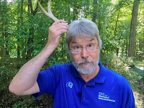 Bob Alderink putting a deer antler on his head.