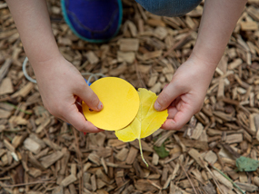 Girl matching yellow circle with yellow leaf.