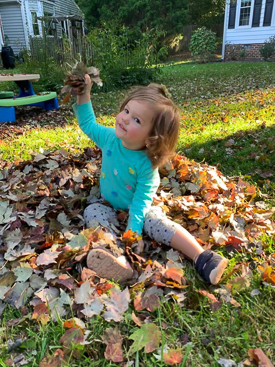 Child playing in a pile of leaves.