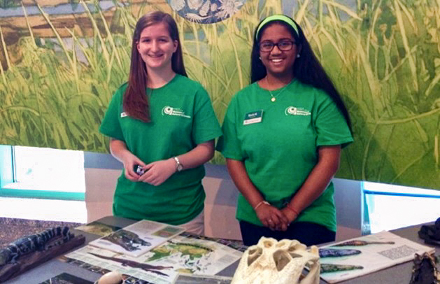 Two teenagers volunteering at a Museum table.