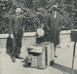 An old photo of two men by scientific equipment