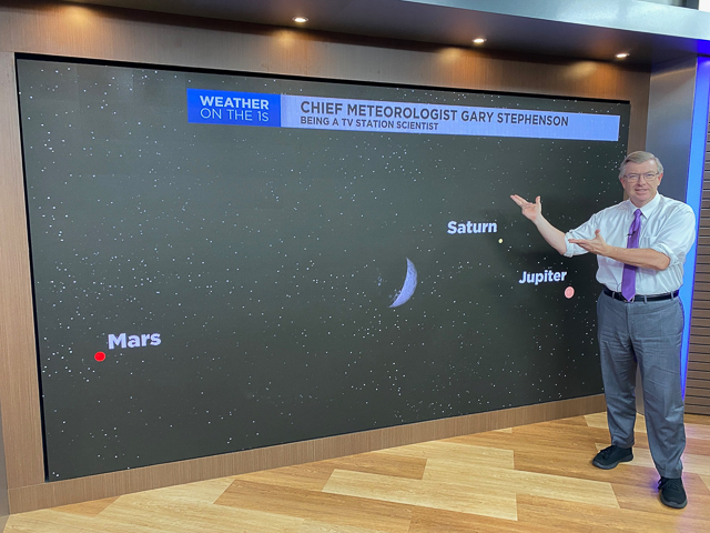 A meteorologist standing by a screen showing planets in the sky