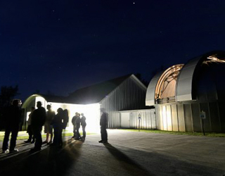 People standing outside an observatory at night
