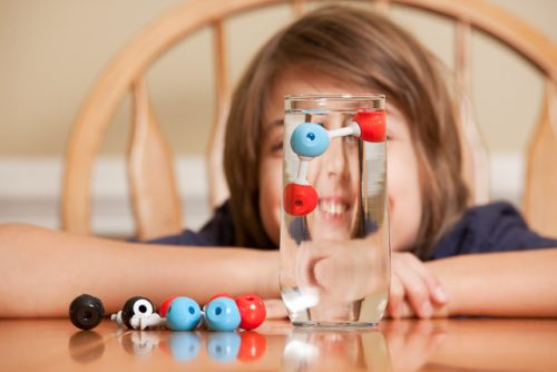 Boy With H2O Molecule Model in Water Glass