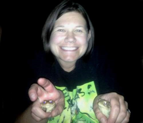 A smiling woman holding two frogs, one in each hand