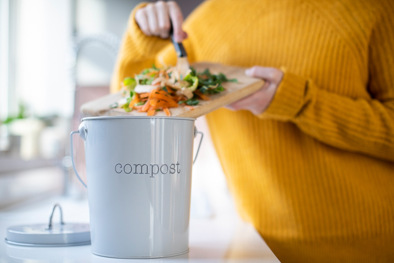 Woman adding vegetable scraps to home compost bucket.