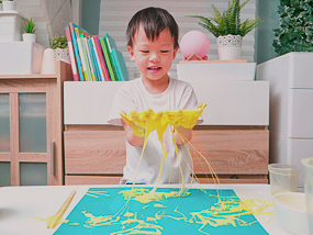 Asian boy playing with sticky paint.