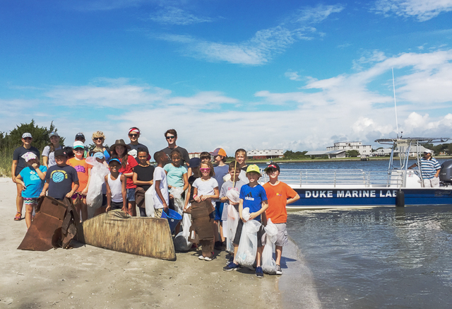 Duke University students and a group of kids with trash bags full of beach trash.