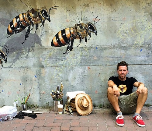 A man sitting by a wall with bees painted on it