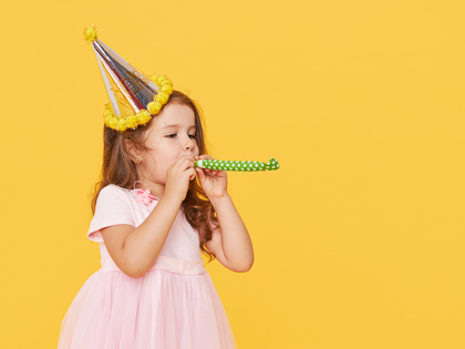 Birthday girl in a dress blowing noisemaker