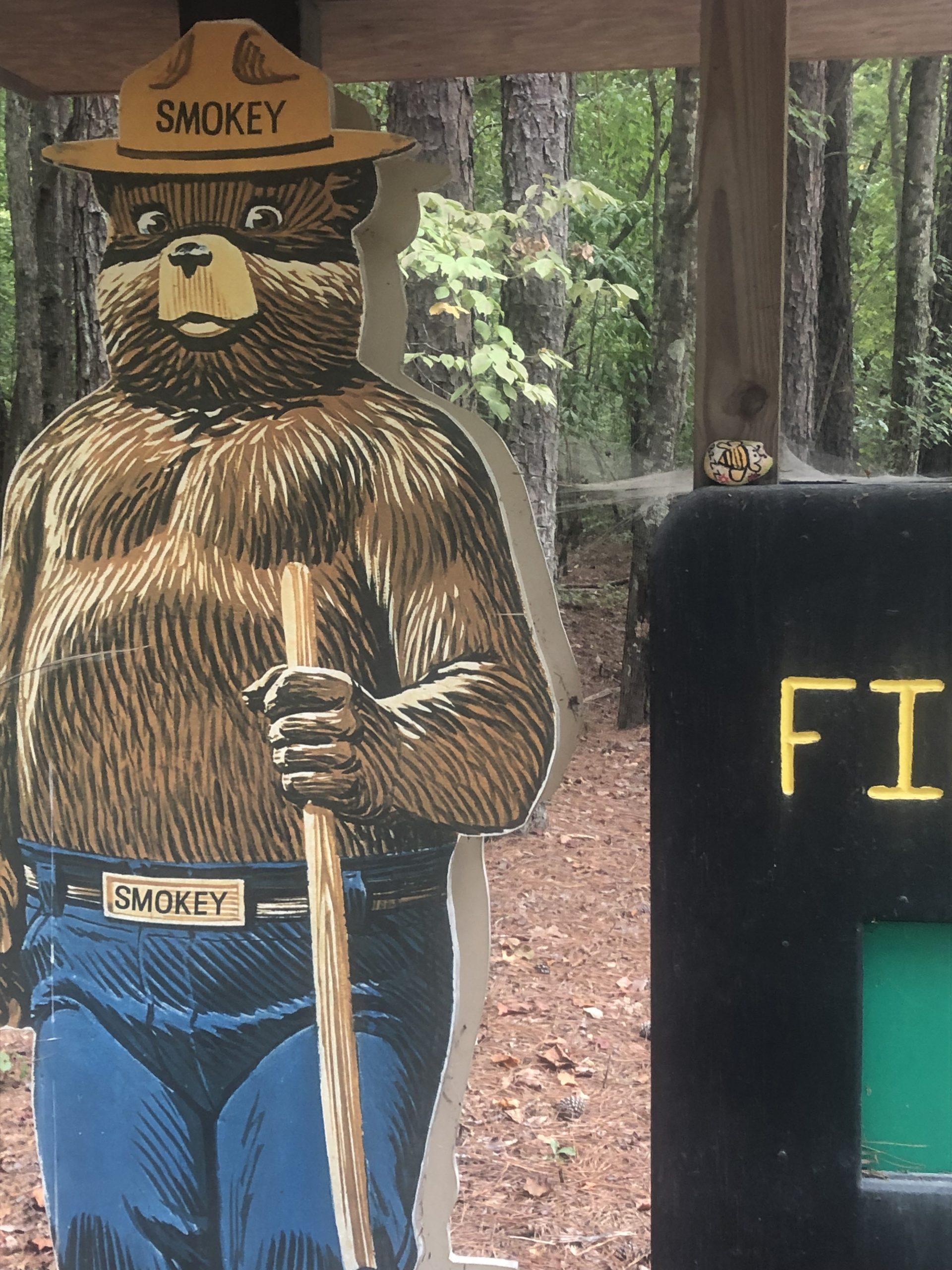 A bee painted like a rock next to Smokey Bear