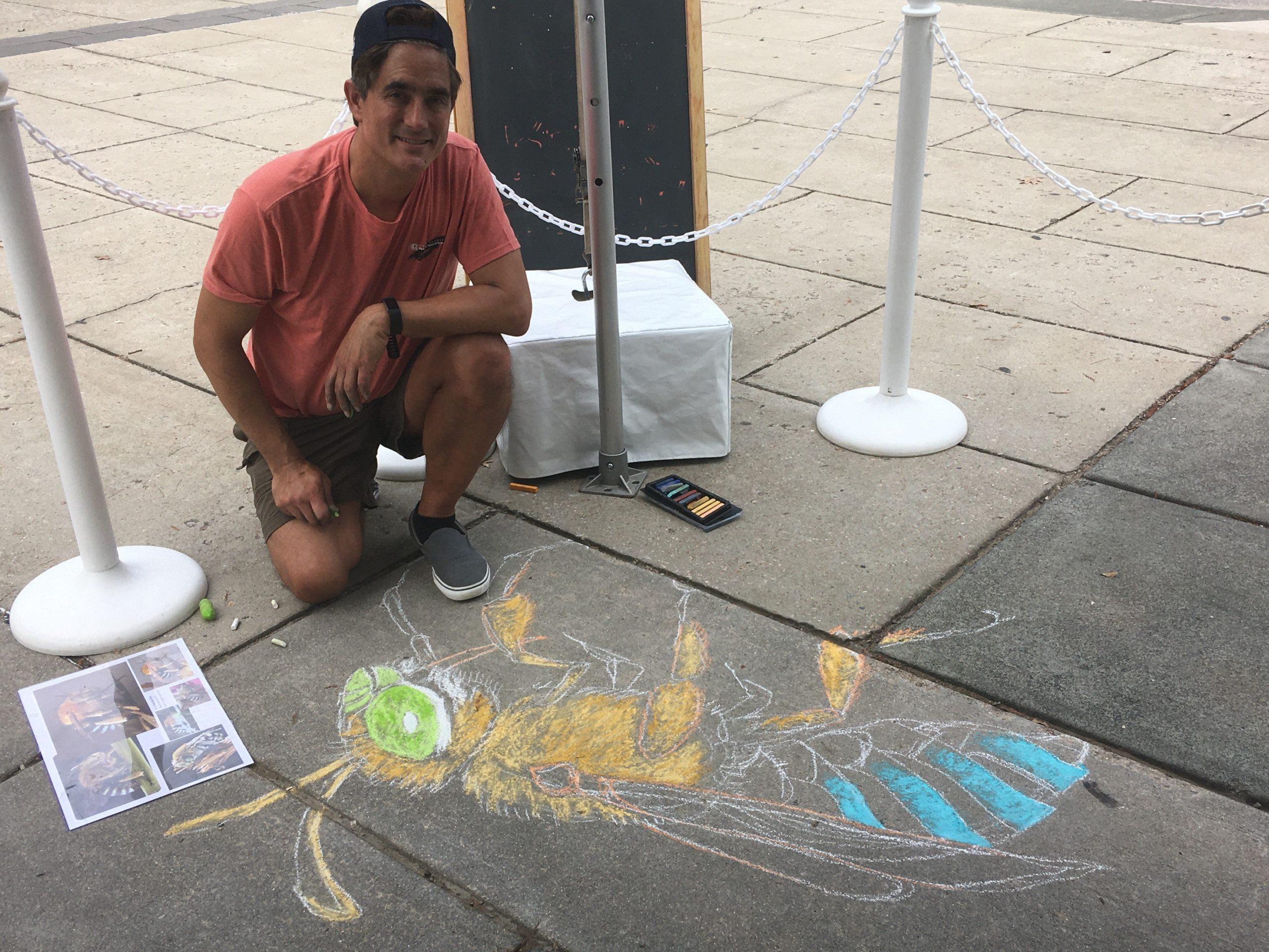 A man squatting next to a chalk sketch on the sidewalk
