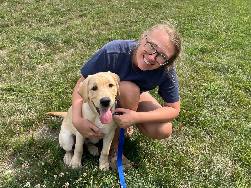 Hannah Salomons with a Lab puppy.