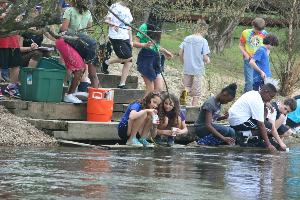 Exploris Middle School students releasing American shad fry