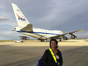 Dr. Smith on the tarmac at the Armstrong Flight Research Center in Palmdale, CA, getting ready to board the SOFIA aircraft to observe massive forming stars.